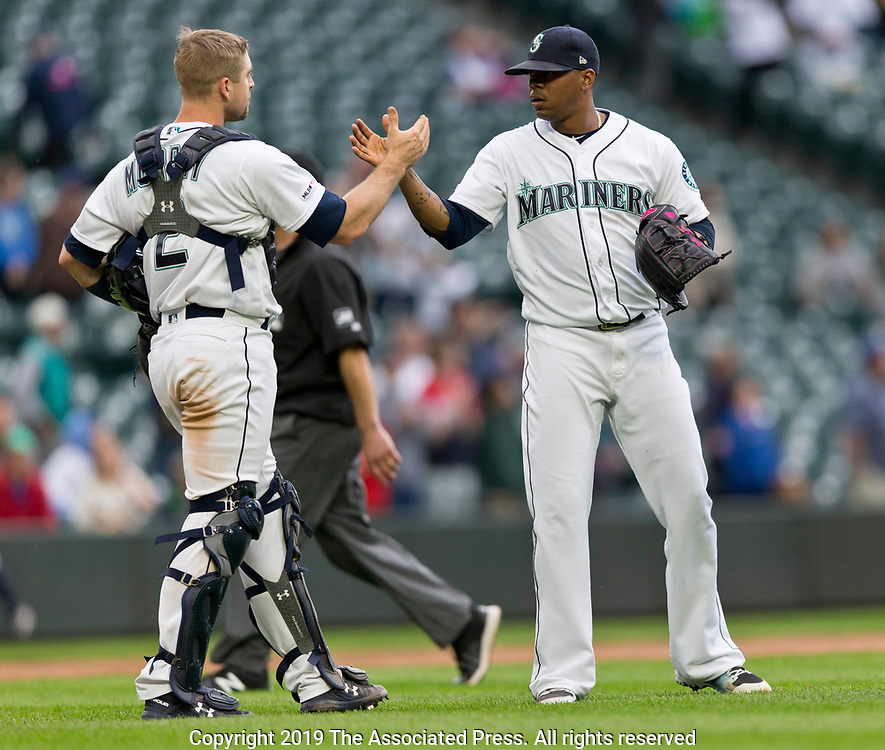 Seattle Mariners closing pitcher Roenis Elias and catcher Tom Murphy shake hands after the 8-2 win over the Kansas City Royals in a baseball game, Wednesday, June 19, 2019, in Seattle. (AP Photo/John Froschauer)