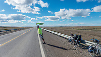 Cyclist leaning into the infamous strong winds of the Patagonian pampa, Argentina