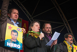 sbury Park, London, March 22 2015. Thousands of London's Kurdish community gather for Newroz, their traditional New year's celebrations. The exiled community mourns the death of Londoner and ex Royal Marine Erik Konstandinos Scurfield, a hero to them, who was killed fighting ISIS, and whose mother Vasiliki Scurfield addressed the crowd. PICTURED: Konstandinos Erik Scurfield's mother Vasiliki delivers a speech as his father Chris, second right, stands by her side.