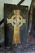 Painted Celtic cross inside 1400s Comlongon Castle, a restored Medieval Scottish tower house dating from the late 1400s. Guests can stay in the attached Edwardian hotel, a baronial style mansion built 1900-02, set in 120 acres of manicured gardens, sweeping lawns, carp pond, lakes and woodlands, near Clarencefield and Dumfries, in southwest Scotland, United Kingdom, Europe. Originally built by the Murrays of Cockpool, Comlongon Castle remained in the Murray family until 1984. The castle is 50 feet square and stands 70 feet high, with walls over 4 meters thick, with impressive displays of weapons, armor and banners.