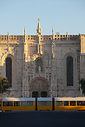 A modern tram passes Jeronimos Monastery in the early hours of the morning in Lisbon, Portugal