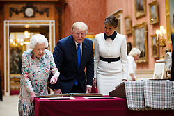 First Lady Melania Trump (right) Queen Elizabeth II (left) with US President Donald Trump view a special exhibition in the Picture Gallery of items from the Royal Collection of historical significance to the US, following a private lunch at Buckingham Palace in London, on day one of his three day state visit to the UK.