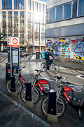 Santander rental bikes await their next riders, in front of a cycling commuter in Shoreditch where graffiti covers the exterior of a former office property, on 26th February 2021, in London, England.