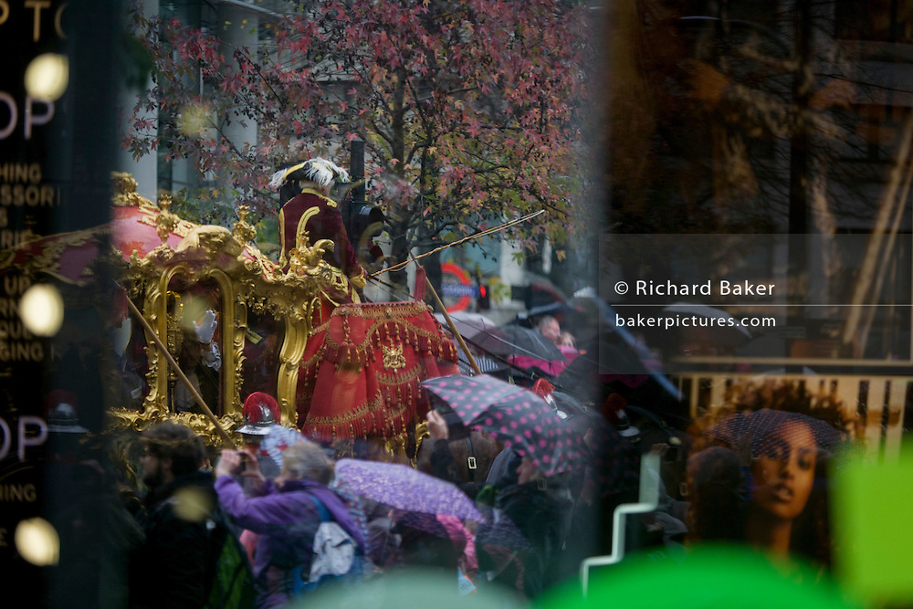 Seen through a shop window, the new Lord Mayor Jeffrey Mountevans rides through the streets of the City of London, the capital's ancient financial district founded by the Romans in the 1st Century. This is the pageant's 800th birthday and the 250 year-old horse-drawn guided State Coach will be pulled through the medieval streets with the newly-elected Mayor along with 7,000 others. This first took place in 1215 making it the oldest and longest civil procession in the world which survived both Bubonic plague and the Blitz.