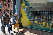 As the coronavirus restrictions continue, the process of easing people pass a giant inflatable yellow flamingo in the window of EE phone shop as more people begin to come to the city centre on 2nd June 2021 in Birmingham, United Kingdom. After months of lockdown, the first signs that life will start to get back to normal begin, with more people enjoying the company of others in public, as the rule of six starts the first stage of lockdown ending.