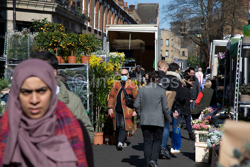 Columbia Road flower market on Mothers Day, and its last open Sunday for a while due to Covid-19 on what would normally be a busy, bustling market day with hoards of people out to buy flowers and socialise, the numbers of people out is a fraction of a regular Sunday on 22nd March 2020 in London, England, United Kingdom. All of the East End Sunday markets have been affected by the Coronavirus outbreak, with some completely closed and some currently partially open. Coronavirus or Covid-19 is a new respiratory illness that has not previously been seen in humans. While much or Europe has been placed into lockdown, the UK government has announced more stringent rules as part of their long term strategy, and in particular social distancing.