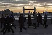 Commuters cross London bridge with Tower Bridge in the background to get to work in the city of London.