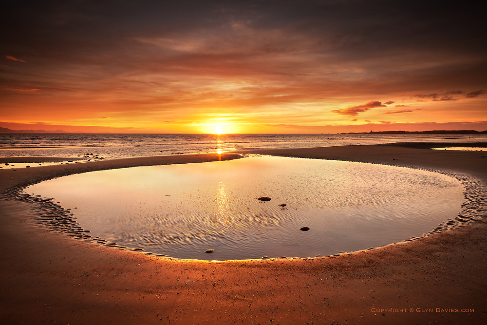 Sunset over textured and patterened wet sand at Llanddwyn Beach, West Anglesey, Irish Sea,