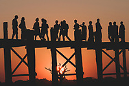 Amarapura, Myanmar - November 9, 2011: As the sun sets, fifteen men and women of various ethnicities stand on a section of the U Bein Bridge in Amarapura, a township of Mandalay city that was once the capital of Myanmar. This bridge was built around 1850 and, at 1.2 kilometers, is one of the longest teakwood bridges in the world.