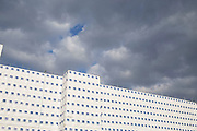 A large commercial building project under wraps while it is in the construction phase. The colour of the sky and clouds is mirrored by the colour of the platsic hoarding which the building is wrapped in. London, UK.