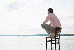Young man sitting chair lake alone thoughtful