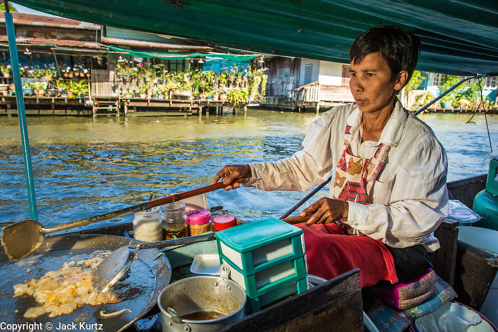 13 JANUARY 2013 - BANGKOK, THAILAND:  A woman makes oyster omelets on her boat on Khlong (Canal) Bang Luang in Bangkok. The Bang Luang neighborhood lines Khlong (Canal) Bang Luang in the Thonburi section of Bangkok on the west side of Chao Phraya River. It was established in the late 18th Century by King Taksin the Great after the Burmese sacked the Siamese capital of Ayutthaya. The neighborhood, like most of Thonburi, is relatively undeveloped and still criss crossed by the canals which once made Bangkok famous. It's now a popular day trip from central Bangkok and offers a glimpse into what the city used to be like.    PHOTO BY JACK KURTZ