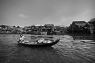 A middle age asian woman rows her tiny barge on a river lined with wooden stilt houses. Cambodia, Asia