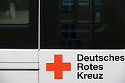 Deutsches Rotes Kreuz - DRK (German Red Cross) vehicle logos at their administrative HQ, 58 Carstennstrasse, Berlin. The International Red Cross and Red Crescent Movement, with its 187 National Societies, is the world's largest humanitarian network. The German Red Cross is part of this universal community, which started 150 years ago to deliver comprehensive aid to people affected by conflict, disaster, sanitary emergencies, or social hardship, guided solely by their needs. Around four million volunteers and members support the Red Cross in Germany alone. From the chapter entitled 'A life to save' and from the book 'Risk Wise: Nine Everyday Adventures' by Polly Morland (Allianz, The School of Life, Profile Books, 2015).