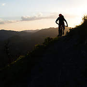 Andrew Whiteford silhouetted at sunset with wildflowers during the summer months in the Tetons. Mail Cabin Trail.