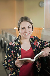Portrait of young woman waiting with book, smiling