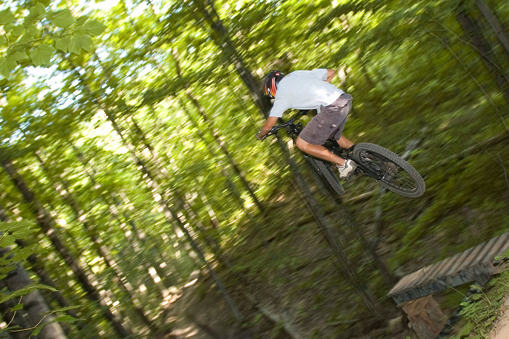 A mountain biker jumps off a wooden structure while freeriding near Marquette, Michigan.