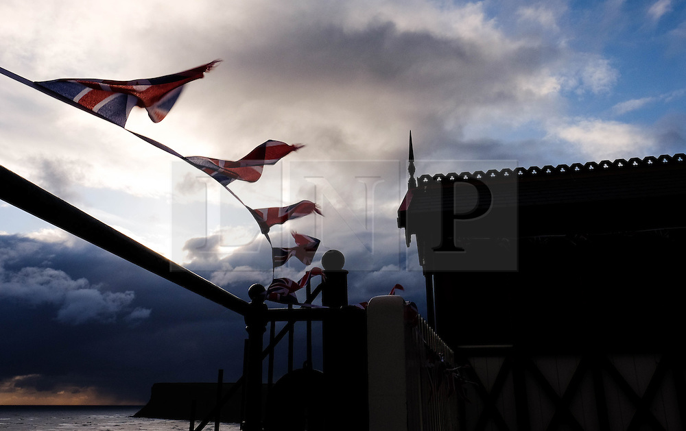 © Licensed to London News Pictures. 24/04/16<br /> Saltburn by the Sea, UK. <br /> <br /> Bunting fastened to railings blows in the wind as sunlight breaks through storm clouds over cliffs at Saltburn by the Sea. Temperatures dropped over the weekend as cold air blew down from the arctic.   <br /> <br /> Photo credit : Ian Forsyth/LNP