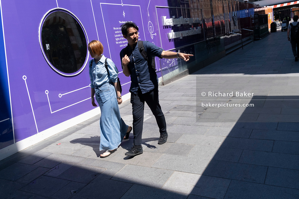 Two pedestrians walk past a purple hoarding that screens off refurburshment works in the West End's Leicester Square, on 16th July 2021, in London, England.