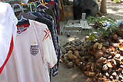 A fake England football shirt hangs out to dry on a clothes line near coconut husks on Meedu Island, Republic of Maldives