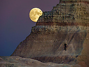 Moonrise at sunset near Ben Reifel Visitor Center in Badlands National Park, South Dakota, USA. The intricately carved cliff of the Badlands Wall constantly retreats as it erodes and washes into the White River Valley below.