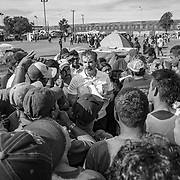 Asylum seekers from Central America who traveled through Mexico to the US border listen to lawyers & legal advisors from Al Otro Lado at Deportivo Benito Juarez in Tijuana. The sports facility was turned into a migrant shelter.