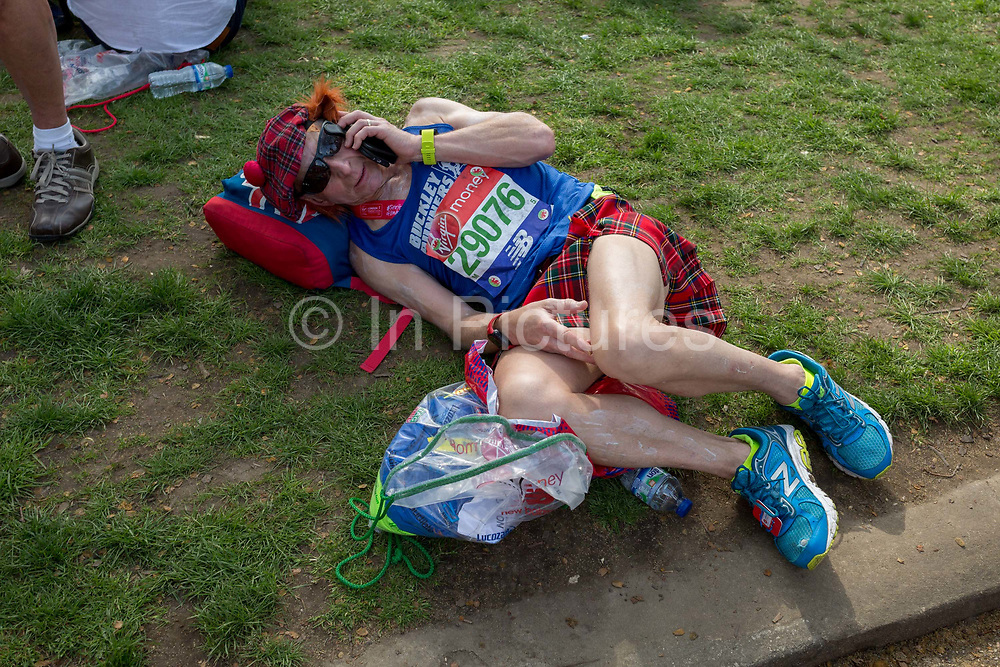 A tired long-distance runner wearing a kilt rests after finishing the London Marathon, in St Jamess Park, on 22nd April 2018, in London, England.