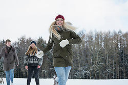 Friends running in snowy landscape in winter, Bavaria, Germany