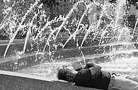 Man who found a refreshing spot near the fountains at Columbus Circle in New York City