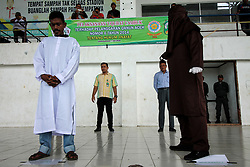 July 5, 2018 - Lhokseumawe, Aceh, Indonesia - An Acehnese man was whipped for violating Sharia law in Lhokseumawe on 5 July 2018, Aceh, Indonesia...According to reports, six Acehnese was sentenced to 25 to 40 whipping strokes, due to online prostitution. Whipping is one form of punishment imposed in Aceh for violating Islamic sharia law. Aceh is the only province in Indonesia that implements Sharia law as a positive law. (Credit Image: © Fachrul Reza/NurPhoto via ZUMA Press)