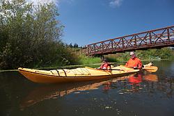 North America, United States, Washington, Bellevue, man and son (age 6) kayaking under bridge in Mercer Slough Nature Park.  MR