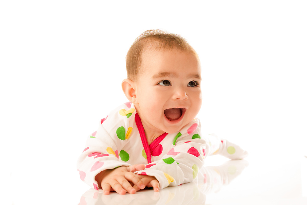 6 month old baby girl crawling on white background.