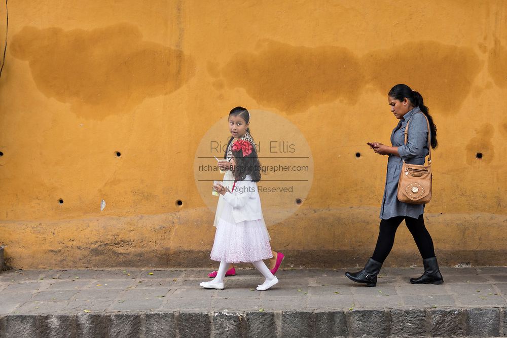 Young Mexican girls walk ahead of their mother after attending confirmation in San Miguel de Allende, Mexico.