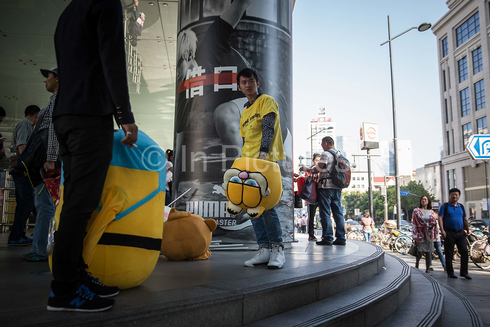 Street promoters holding cartoon character masks prepare to work while standing on a street corner in Shanghai, China, on Friday, Oct. 2, 2015.