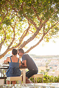 Couple sitting on chairs at restaurant under tree, Paphos, Cyprus