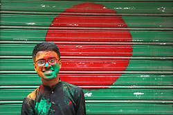 A happy boy stands in front of a shutter of a shop which is painted like a Bangladeshi National flag in Holi festival in the street of Shakhari Bazaar, Dhaka, Bangladesh on 21, March'2019.