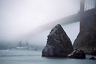 Coast Guard cutter Boutwell sailing under the fog covered Golden Gate Bridge, San Francisco Bay, California