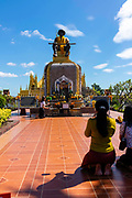 Women pay their respect at the King Setthathirath Statue, Pha That Luang Stuppa, Vientiane, Laos.