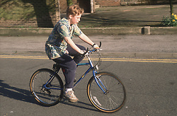 Young boy riding bicycle along street,