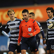 Referee Edvin Jurisevic in besieged by Sporting KC players after awarding a penalty to NYCFC but overturned his ruling after consulting his linesman during the New York City FC Vs Sporting Kansas City, MSL regular season football match at Yankee Stadium, The Bronx, New York,  USA. 27th March 2015. Photo Tim Clayton