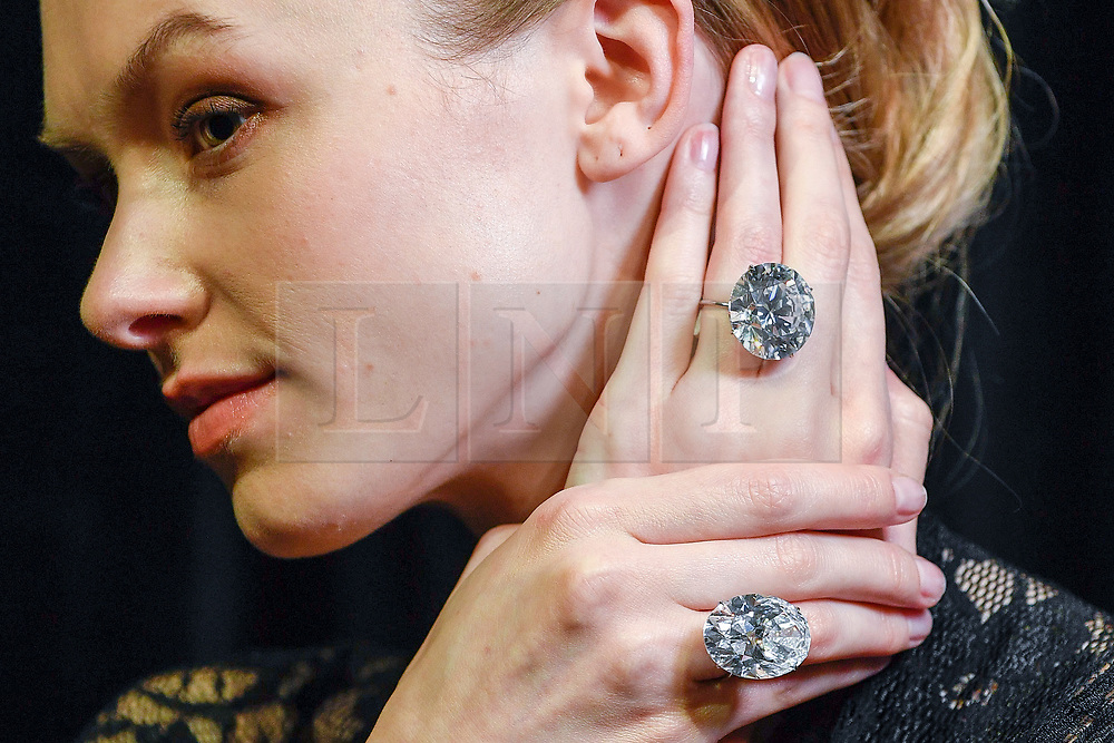© Licensed to London News Pictures. 06/04/2018. LONDON, UK. A model presents a 51.71-carat round brilliant-cut diamond (top) and a 50.39-carat oval diamond (bottom) at a photocall at Sotheby's, New Bond Street. They are two of the largest, purest white diamonds ever to come to auction, have a combined estimate in excess of US$15m and will be sold at auction in Geneva on 15 May.  Photo credit: Stephen Chung/LNP