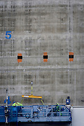 Workmen in cradle on concrete wall of construction development in the City of London