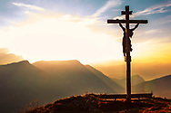 Crucifix on the mountain hill at sunset hour