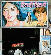Workers underneath a handpainted movie poster, Lucknow, Uttar Pradesh, India