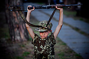 A young boy participating to the ultra-nationalistic Azovets children's camp is being disciplined and required to hold a genuine assault rifle over his head, near the village of Buzova, 30 km west of Kiev, the capital of Ukraine.