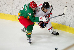 Anton Korneiciuk of Lithuania vs Konstantin Komarek of Austria  during the ice hockey match between National teams of Lithuania (LTU) and Austria (AUT) at 2011 IIHF World U20 Championship Division I - Group B, on December 12, 2010 in Ice skating Arena, Bled, Slovenia.  (Photo By Vid Ponikvar / Sportida.com)