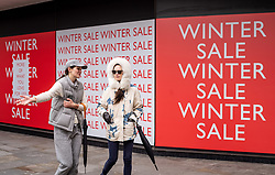 © Licensed to London News Pictures. 18/02/2021. London, UK. Members of the public walk past Winter Sale signs at the Peter Jones store in Chelsea, South West London as Downing Street mulls over how and when to unlock the country from coronavirus restrictions. Yesterday, Prime Minister Boris Johnson revealed that the relaxation of restrictions would be done in stages and would focus on the data not on dates for the easing of lockdown with pubs and hospitality being the last to reopen. Photo credit: Alex Lentati/LNP