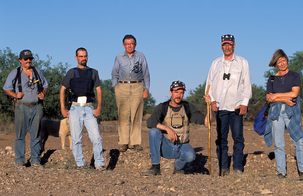 """Chris Simcox, kneeling,  helped found the Minutemen, a group of anti illegal immigration advocates who spend time along the U.S.-Mexico border patrolling for undocumented migrants. Simcox helped launch the organization by issuing a """"Call to Arms"""" in the local Tombstone Tumbleweed publication he owned in Tombstone, Arizona. Please contact Todd Bigelow directly with your licensing requests."""