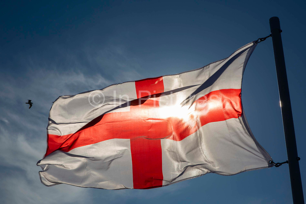 England Flag, the Saint George's Flag flying against a blue sky with the sunshine coming through it.  Folkestone, Kent. United Kingdom.