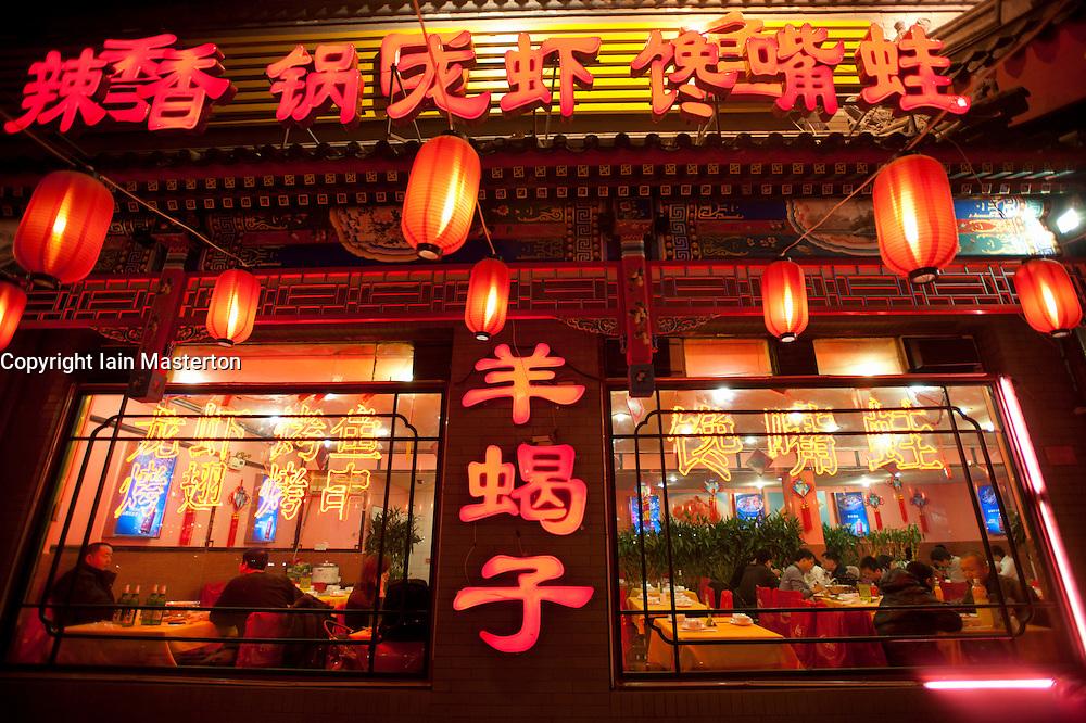 Neon signs and red lanterns at night  illuminating menu at Chinese restaurant in Beijing China